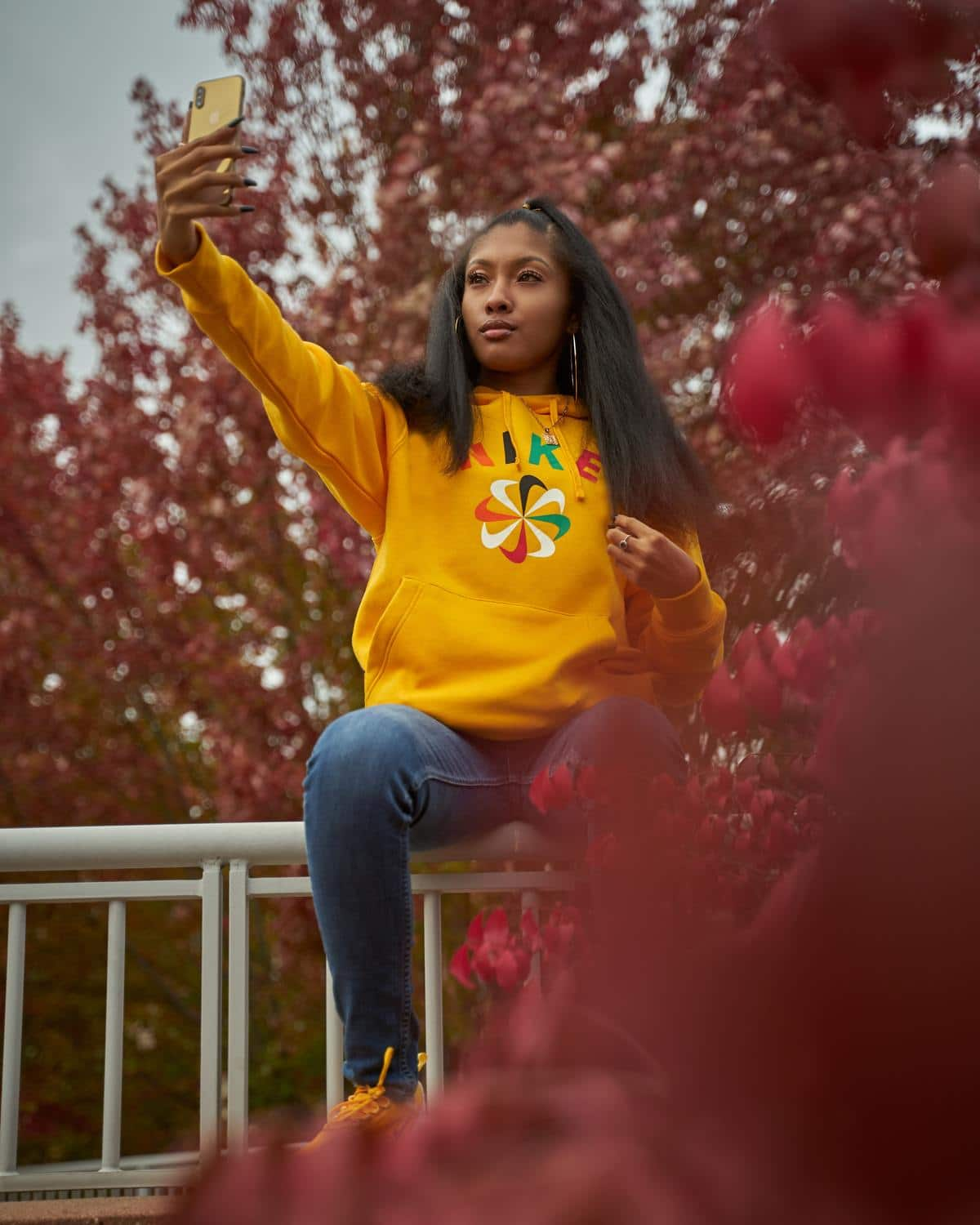 Woman in a Yellow Sweatshirt Sitting on a Fence Looking Good 'AF'