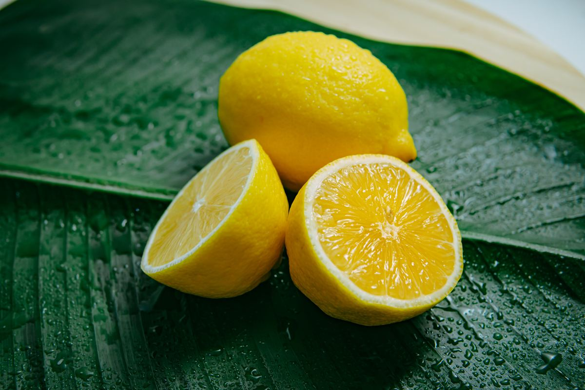 A Whole and Lemon Cut in Two on a Leaf