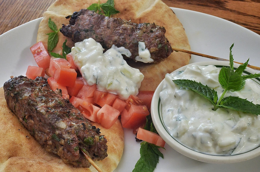 2 Gyros with Tzatziki Sauce on Them, with a bowl of tzatziki beside.