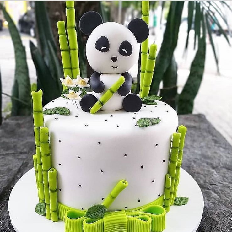 Cute panda bear sitting on top of a white cake surrounded by bamboo