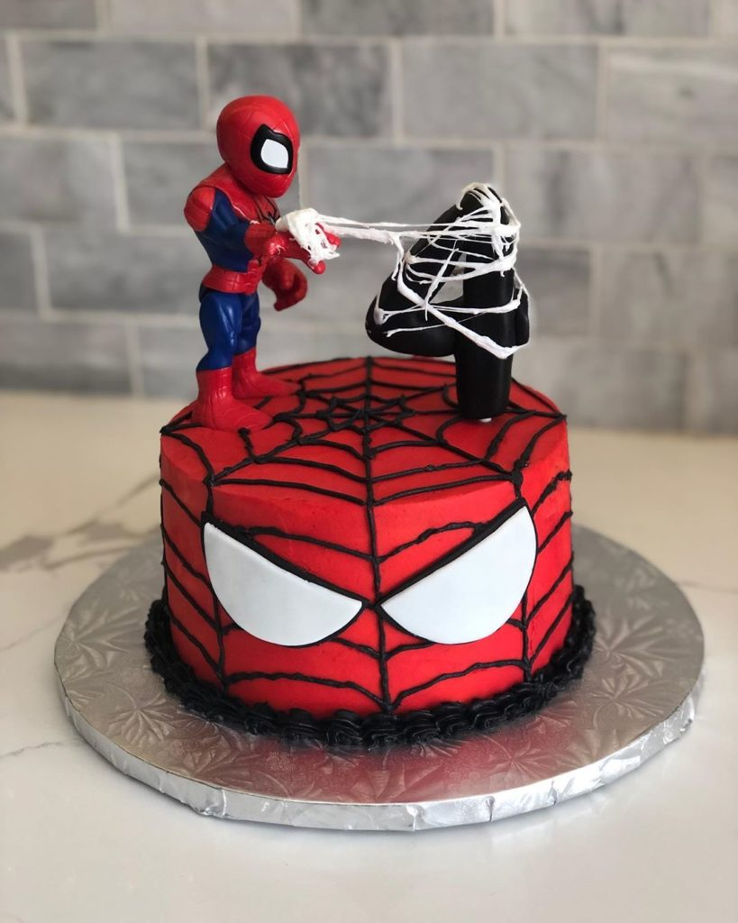 Spiderman cake with a small Spiderman standing on his face