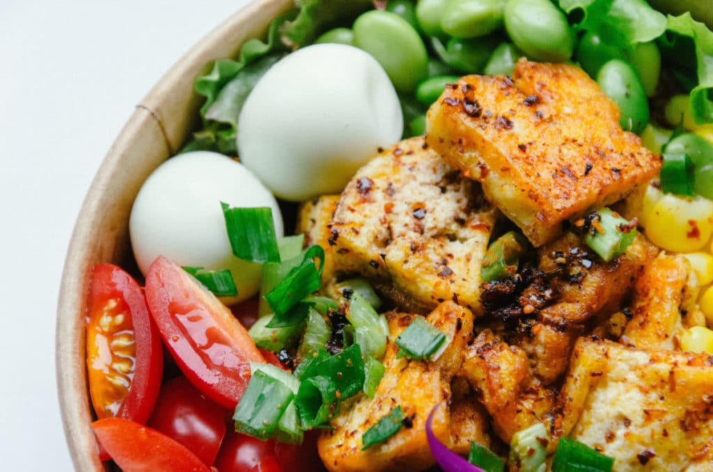 Cooked tofu in a bowl with eggs and other vegetables