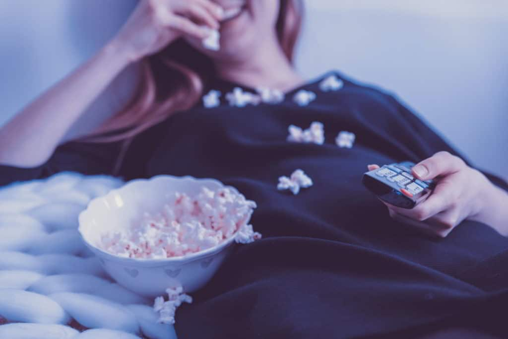 A Woman Eating a Bowl of Popcorn in Bed
